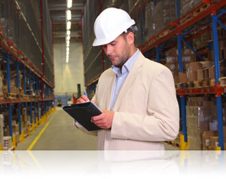 Warehouse worker reviewing inventory on shelves, Fishbowl Inventory Blog