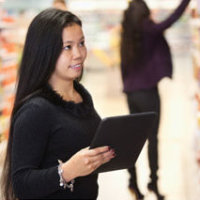 Woman searching for products at a grocery store, Fishbowl Inventory Blog
